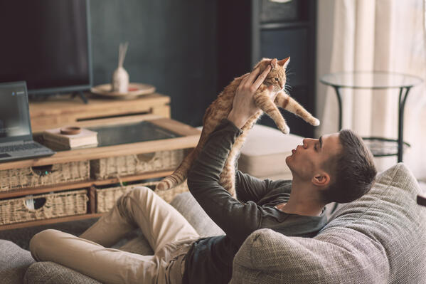 Man holding cat on couch